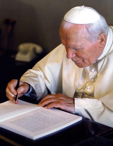 El santo Papa Juan Pablo II firma una de sus encíclicas