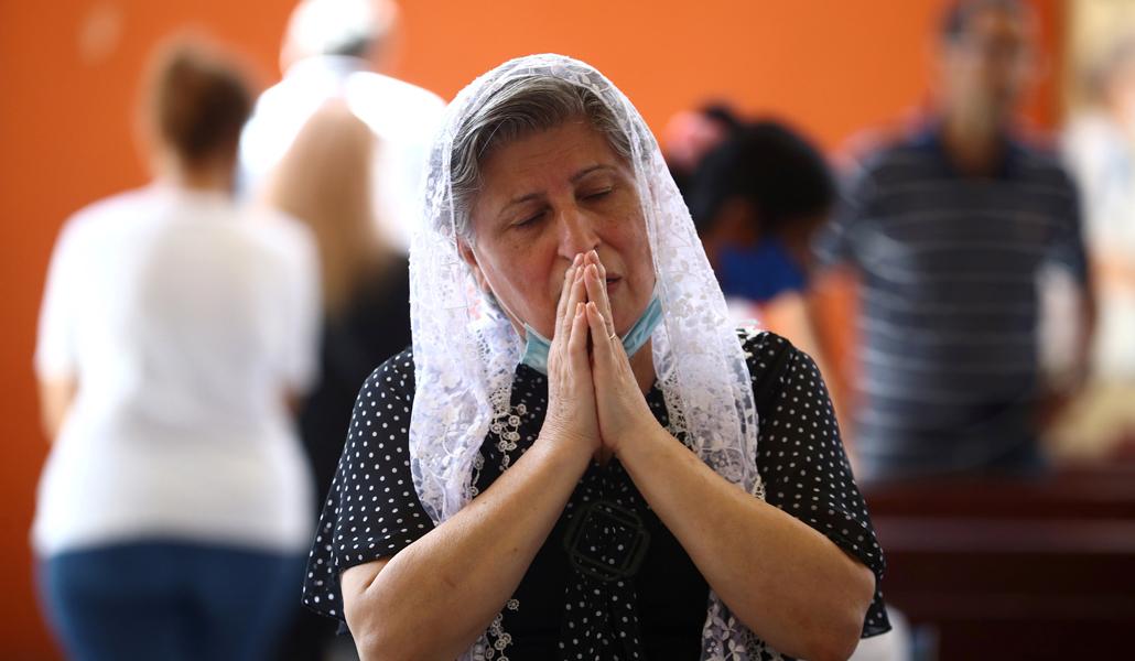 Una mujer reza en una iglesia del Líbano